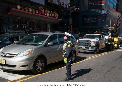 New York, NY - April 3, 2019: New York City traffic policewoman stands in the middle of 42nd street in Times Square directing traffic.