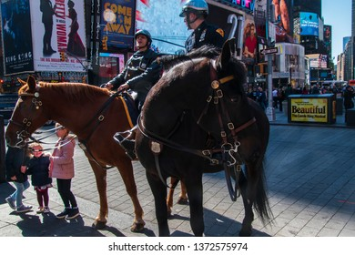 New York, NY - April 3, 2019: Horizontal front view of two mounted New York City policemen in Times Square talking to tourists