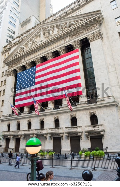 New York, NY: August 27, 2016: Flag draped NYSE on Wall Street. The New York Stock Exchange (NYSE) is the largest stock exchange in the world by market cap.