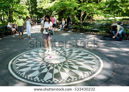 "New York, NY: August 28, 2016: Woman in Strawberry Fields memorial looks at the ""Imagine"" memorial.  Strawberry Fields is a 2.5 acre portion of Central Park dedicated to John Lennon."