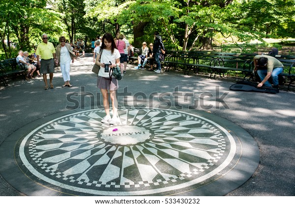"""New York, NY: August 28, 2016: Woman in Strawberry Fields memorial looks at the """"Imagine"""" memorial.  Strawberry Fields is a 2.5 acre portion of Central Park dedicated to John Lennon."""