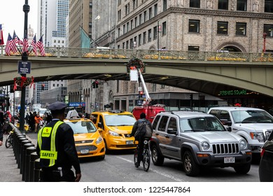 NEW YORK, NY - DECEMBER 01, 2014:  Pershing Square near Grand central terminal in New York City  with trafic and man hanging christmas decoration on bridge.