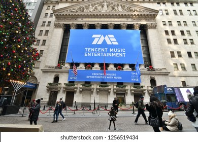 NEW YORK, NY - DECEMBER 12, 2018: Fearless Girl Statue is staring down the New York Stock Exchange during the Tencent IPO. A blue TME banner is displayed across the NYSE building in a wide view.