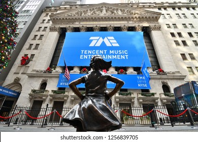 NEW YORK, NY - DECEMBER 12, 2018: Fearless Girl Statue is staring down the New York Stock Exchange during the Tencent IPO. A blue TME banner is displayed across the NYSE building in a full view.