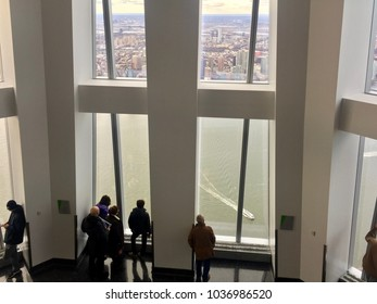 NEW YORK, NY - DECEMBER 20, 2017: Visitors stand by huge windows and look out at Hudson River from the Freedom Tower One World Observatory in New York City.