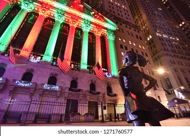 NEW YORK, NY - DECEMBER 23, 2018: Fearless Girl Statue is staring down the New York Stock Exchange during the holidays at night.