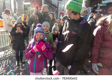 New York, NY - December 29, 2017: Young girl collects confetti during test Air Worthiness of Confetti on Times Square for New Year celebration from atop of Hard Rock Cafe Marquee