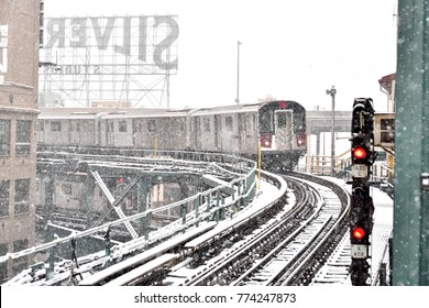 NEW YORK, NY - DECEMBER 9, 2017: The 7 train approaches the station with the iconic Silvercup Studios sign in the background during a snow storm.
