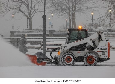NEW YORK, N.Y. – February 1, 2021: A snow removal vehicle passes a pedestrian in Lower Manhattan during a winter storm.