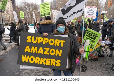 NEW YORK, NY - FEBRUARY 20, 2021: Protestors hold signs and march on a picket line across from Amazon's Whole Foods Market in solidarity with the unionizing Amazon workers in Bessemer, Alabama.