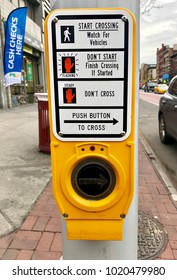 New York, NY - FEBRUARY 6, 2018: Automated yellow street crossing sign with push button helping to cross safely on a busy New York City street in Harlem.