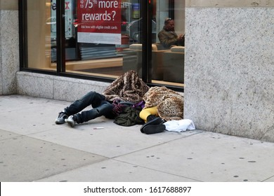 New York, NY - January 15, 2020: Couple sleeping rough near Times Square, under faux leopard fur coats in winter