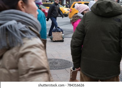 New York, NY - January 4, 2017: Homeless population swelled during first term of Bill de Blasio as mayor of New York. People walk by homeless on streets of Manhattan.