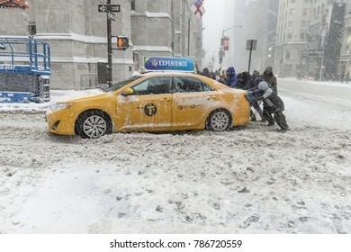 New York, NY - January 4, 2018: People push taxi stuck in snow in Manhattan under heavy snow storm, cold and wind. A giant winter bomb cyclone hit the US East Coast on Thursday