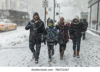 New York, NY - January 4, 2018: People try to navigate streets in Manhattan under heavy snow storm, cold and wind. A giant winter bomb cyclone hit the US East Coast on Thursday