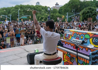 NEW YORK, NY - JUNE 19, 2020: Musician Jon Batiste speaks to gathered crowds between songs as performs live in concert on Juneteenth on the steps of the Brooklyn Public Library at the Grand Army Plaza