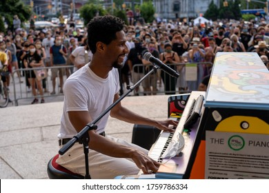 NEW YORK, NY - JUNE 19, 2020: Musician Jon Batiste performs live in concert on Juneteenth on the steps of the Brooklyn Public Library at the Grand Army Plaza.