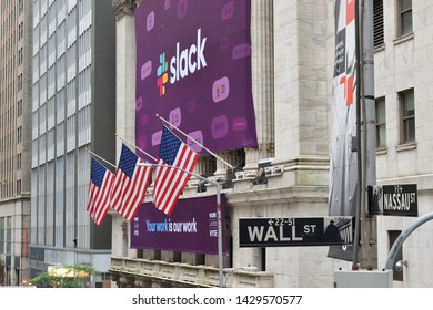 NEW YORK, NY - JUNE 20, 2019: The Slack Technologies Initial Public Offering (IPO) banner on the New York Stock Exchange behind the Wall Street Sign as seen from Federal Hall.