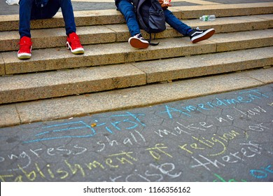 New York, NY; June 2017; People sit on the steps of Union Square with the First Amendment written in chalk on the sidewalk