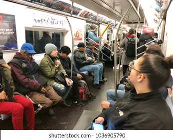 NEW YORK, NY - MARCH 1, 2018: Frustrated subway riders sit in a car and listen to operator's announcement about metro delays in New York City.