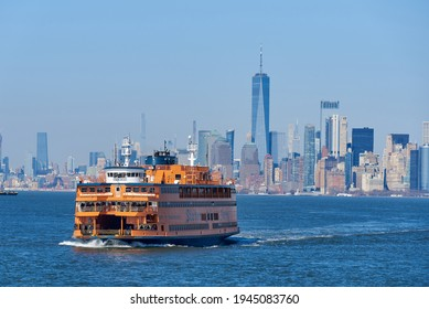 New York, NY - March 21 2021: A Staten Island Ferry, in New York Harbor, steams toward the terminal in St. George, Staten Island. In the background is the skyline of Lower Manhattan, NYC