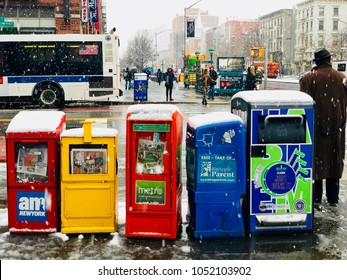NEW YORK, NY - MARCH 22, 2018: Row of colorful newspaper stands in Harlem, New York City during a snow storm.