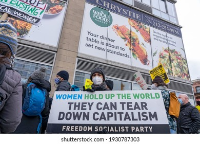 NEW YORK, NY – MARCH 6, 2021: Laundry Workers Center protestors holding signs seen in front of Whole Foods Market on Huston in support of Alabama Amazon Union during a protest of Liox Cleaners.