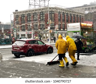 NEW YORK, NY - MARCH 7, 2018: Two maintenance workers wearing yellow waterproof jackets and boots are removing snow from a sidewalk in Harlem during Nor'easter snow storm.