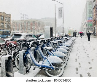 NEW YORK, NY - MARCH 7, 2018: Snow coveres citibikes standing in the dock during Nor'easter snow storm in Harlem, NY.