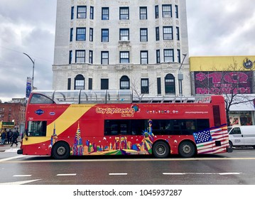 NEW YORK, NY - MARCH 8, 2018: Gray Line New York City sightseeing double Decker red bus passes by the famous Hotel Theresa in Harlem, NY.