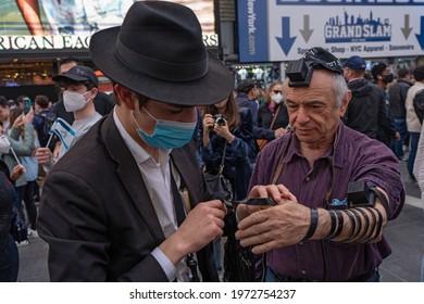 NEW YORK, NY – MAY 12, 2021: A Hasidic Chabad man helps a pro-Israel supporter put prayer Tefillin or phylacteries in Times Square.