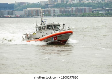 New York, NY - May 28, 2018: US Coast Guards boat crew conduct search and rescue demonstration over open water during Memorial Day celebration at Intrepid Sea, Air & Space Museum