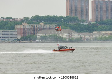 New York, NY - May 28, 2018: US Coast Guards MH-65D Dolphin helicopter crew conduct search and rescue demonstration over open water during Memorial Day celebration at Intrepid Sea, Air & Space Museum