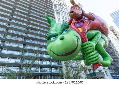 New York, NY - November 22, 2018: Dr. Seuss The Grinch giant balloon floats at 92nd Annual Macy's Thanksgiving Day Parade on the streets of Manhattan in frigid weather