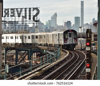 NEW YORK, NY - NOVEMBER 25, 2017: The 7 train approaches the station with the iconic Silvercup Studios sign and Manhattan skyline in the background.