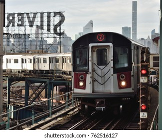 NEW YORK, NY - NOVEMBER 25, 2017: The 7 train arrives at the station with the iconic Silvercup Studios sign and Manhattan skyline in the background.