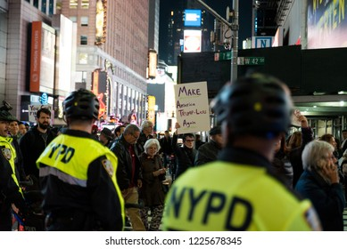 New york, NY - November 8 2018: Protesters take to the streets near times square to march against donald trump in the mueller controversy after sessions got fired. NYPD (Police) on Bikes Department
