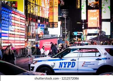 New York, NY - October 19, 2018: Billboards and advertisements in Times Square surround NYPD police patrol cars.