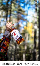 New York, NY - October 19 2019: Woman holding up bottle of Jim Beam bourbon whiskey while camping in the woods
