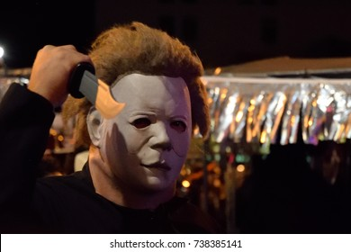 "NEW YORK, NY - OCTOBER 31, 2016: A man dressed up with a scary ""Michael Myers"" mask is posing with a toy knife walking in the Greenwich Village Halloween parade.."