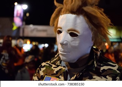 "NEW YORK, NY - OCTOBER 31, 2016: A man dressed in a camouflage uniform with a ""Michael Myers"" mask is walking in the Greenwich Village Halloween parade and scaring people."
