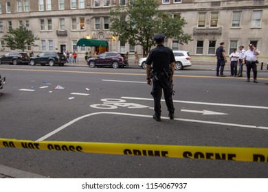 NEW YORK, NY- A police officer stands at the scene of a car accident on Friday, August 10th. A 23-year-old woman was riding in the bicycle lane when she was struck and killed by a garbage truck.