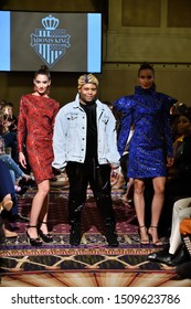 New York, NY - SEPTEMBER 7, 2019: Designer Adonis King poses with twin models on the runway at New York Fashion Showcase SS-20 during NY Fashion Week at the Roosevelt Hotel.