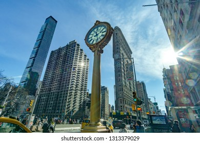 New York, NY / United States - Feb 14, 2019: Landscape view of the Flatiron Building and Street Clock on Fifth Avenue in Manhattan