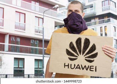 New York, NY / United States - Jul 12 2019: China spying via Huawei. Ban Huawei protest. Man with covered face holds banner with drawn black Huawei logo. Sanctions