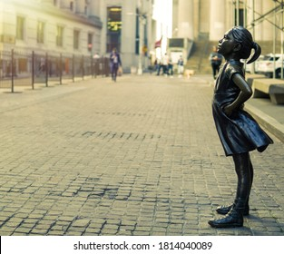 New York, NY / United States - August 20, 2020: Earlier morning profile view of the 'Fearless Girl' statue, by Kristen Visbal, standing on Broad Street in front of the New York Stock Exchange.