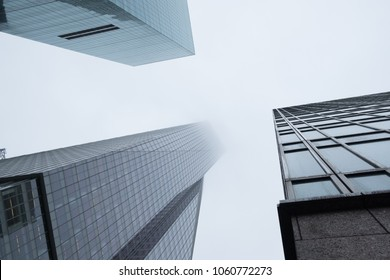NEW YORK, NY - UNITED-STATES May 2017 - Three skyscraper buildings shot from below in New York City on a cloudy day.