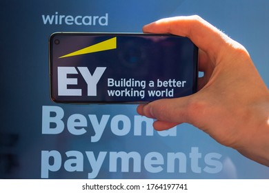 New York. NY / USA - 06 26 2020 : Wirecard.  Hand holding mobile phone with Ey Ernst and Young logo with wirecard website in the background.