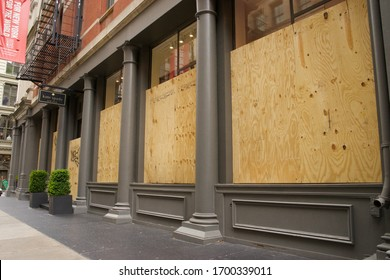 New York, NY / USA - April 10, 2020: In the wake of government ordered COVID-19 closures, luxury goods shops in New York City's trendy SoHo neighborhood have boarded up their large storefront windows.