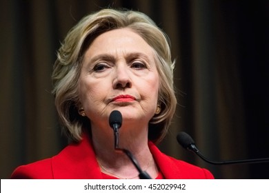 NEW YORK, NY, USA - APRIL 13, 2016: Hillary Clinton in a red suit pauses with a facial expression fit for currency as she gives a speech at the National Action Network's 25th annual convention,